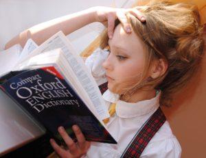 A young student reads her dictionary