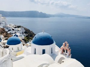 Santorini is famous for its stark white-colored buildings with tones of deep blue that mirror the nation's flag